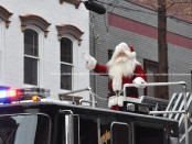 Santa atop the Newton Fire Department ladder truck waves to the crowd. Photo by Jennifer Jean Miller.
