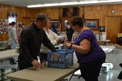 Labor Commissioner Harold J. Wirths (plaid shirt) and his wife, Debbie (white shirt), help volunteers package Thanksgiving meals for nearly 100 needy families as part of an annual food drive coordinated by the Sussex Help Center. Image provided.