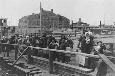 Immigrants entering Ellis Island in 1902. Public domain image.