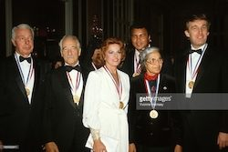 A 1986 photo shows Joe DiMaggio (far left) as an award recipient of the Ellis Island Medal of Honor with Donald Trump (far right). Pictured from left to right are: DiMaggio, Victor Borge, Anita Bryant, Muhammad Ali, Rosa Parks and Trump. Image courtesy of Getty Images.