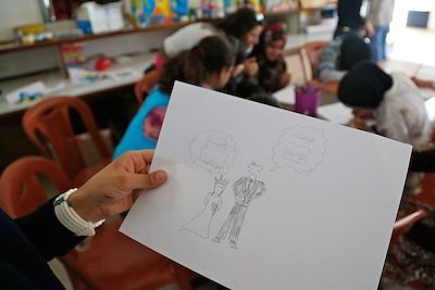 A child holds up a drawing in a Syrian refugee camp where she shows a young bride appearing sad and thinking of school, while a groom smiles and thinks of a home. Creative commons image.