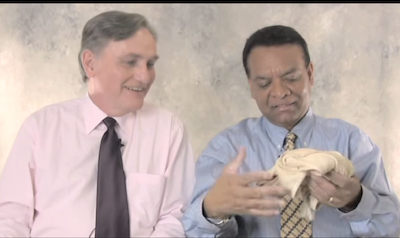 Stanley Praimnath holds up his tattered undershirt that covered his torso on 9/11/01, which he keeps with a pair of shoes and prescription that helped him through that difficult day when the two became friends. Image courtesy of Guideposts/YouTube.