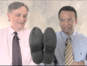 Stanley Praimnath and Brian Clark, who became friends after Clark rescued Praimnath on 9/11/01, marvel at the condition of Praimnath's shoes from the events that day. Image courtesy of Guideposts/YouTube.